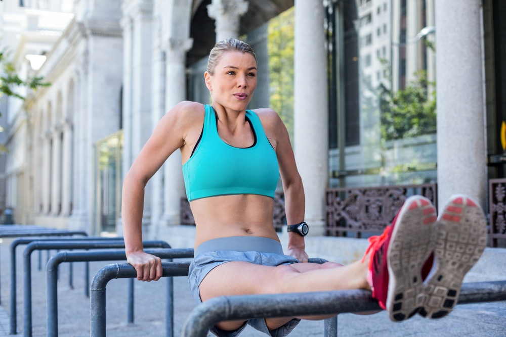 A beautiful knock knees athlete woman stretching her body against pipes on a sunny day.jpeg