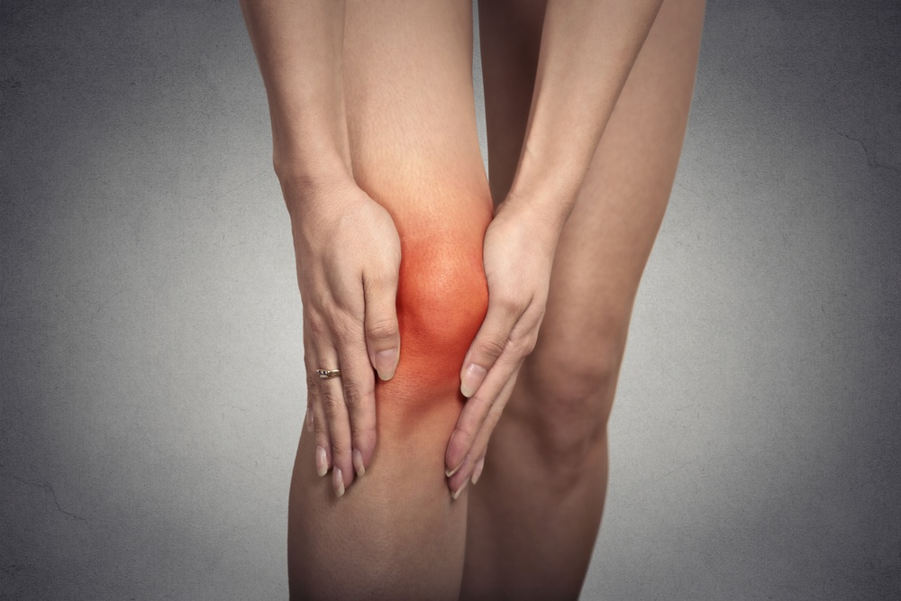 Closeup knee joint problems on woman leg indicated with red spot isolated on gray background. bow legs cause knee pain..jpeg