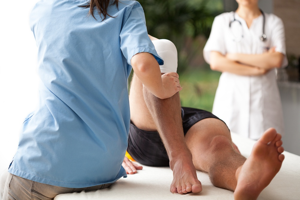 Female orthopedic specialist helping to exercise the patient injured knee.jpeg