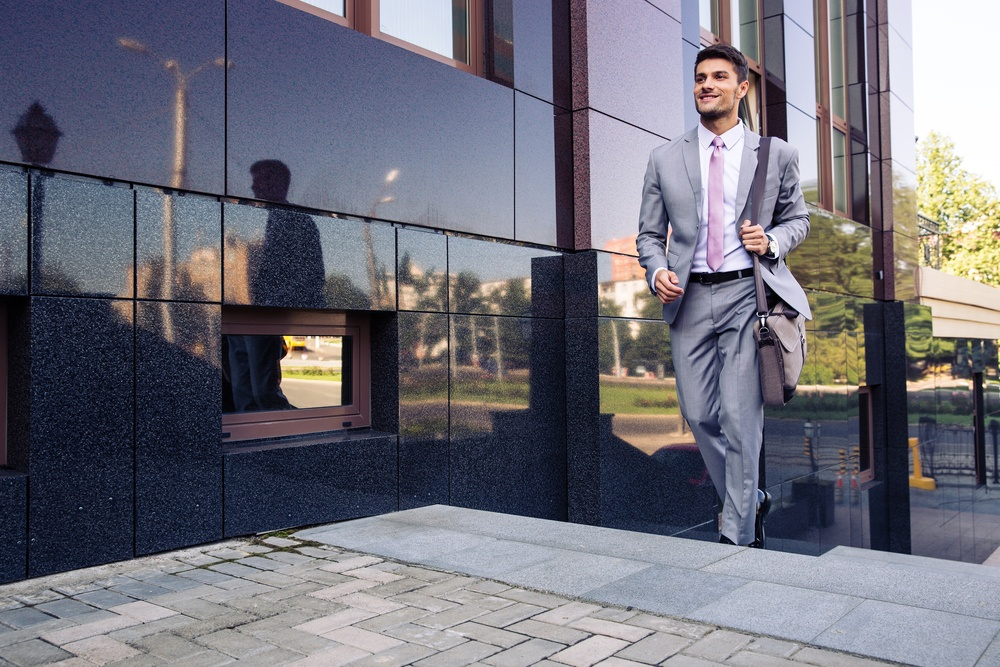 Happy businessman walking on stairs outdoors height legnthening success.jpeg