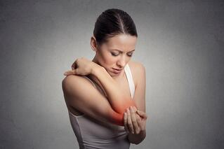 Joint inflammation indicated with red spot on female's elbow. Arm pain and injury concept. Closeup portrait woman with painful elbow on gray background .jpeg