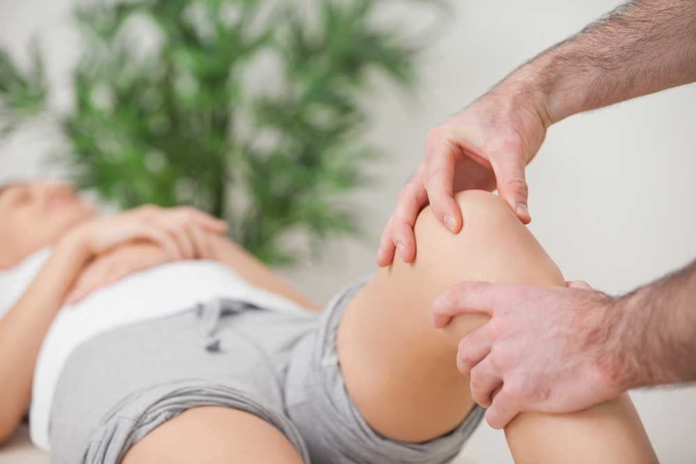 Practitioner using his fingers to massage a knee in a room.jpeg