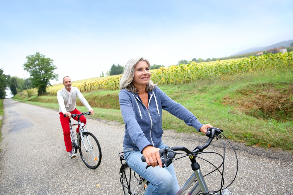 Senior couple riding bicycle in countryside.jpeg