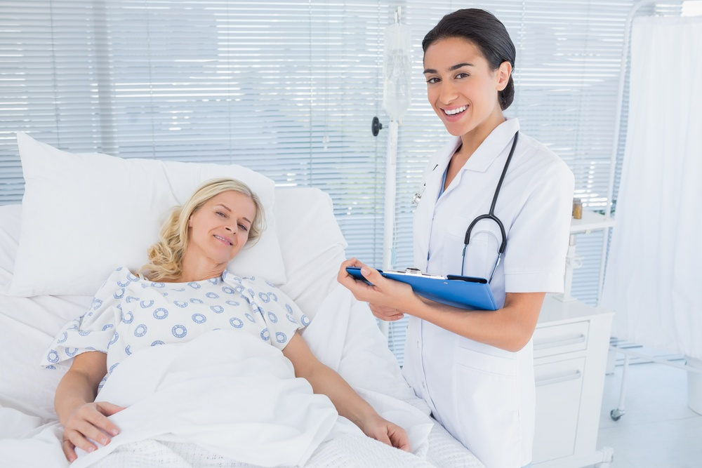 Smiling doctor standing next to her patient in hospital room.jpeg