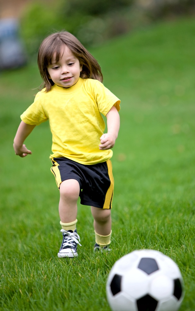 happy kid playing football in a park outdoors. bow legs diagnoses.jpeg