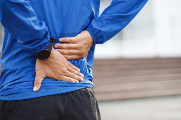 closeup man holding lower back in pain