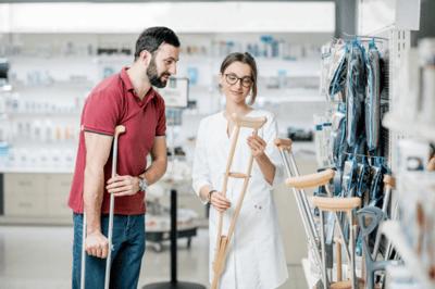 man and woman looking at crutches