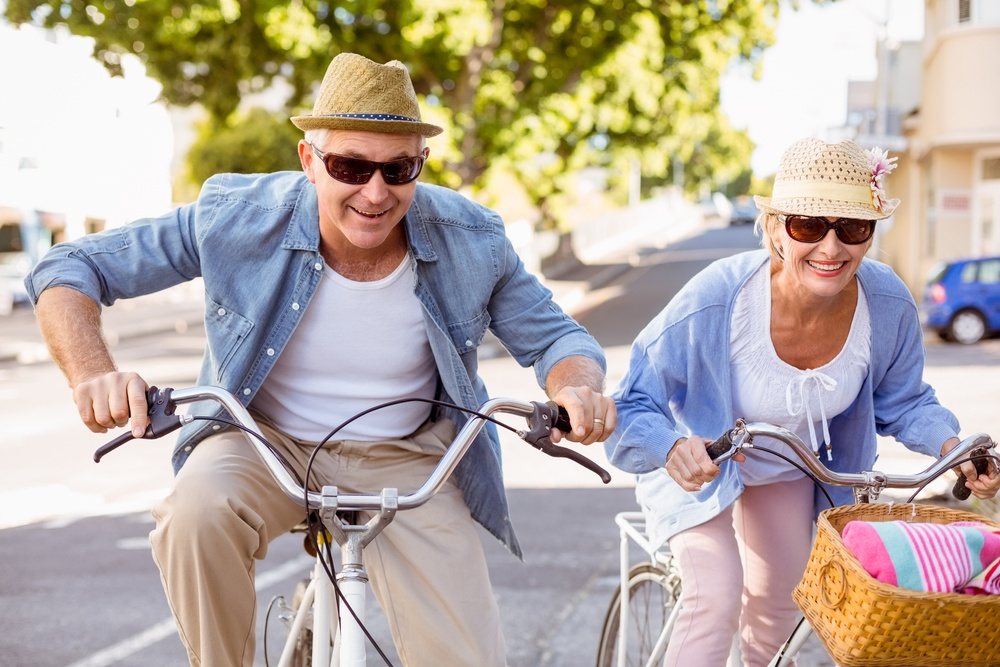 Happy mature couple going for a bike ride in the city on a sunny day.jpeg